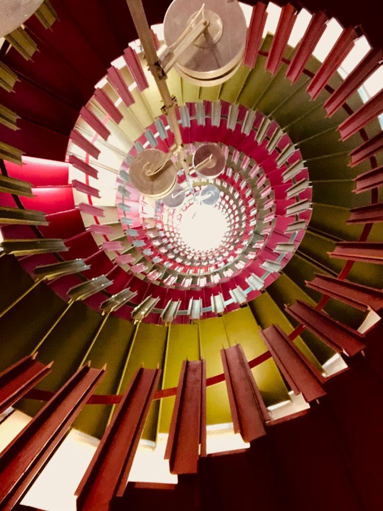 Ansicht einer Wendeltreppe von oben in Rot und Gelb.