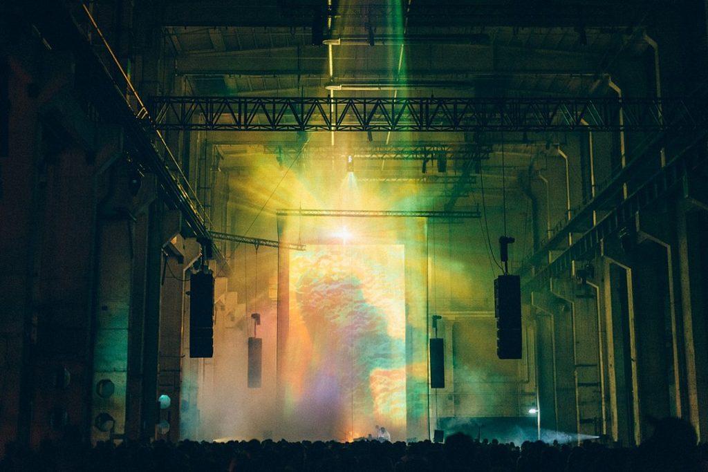 Eine Licht und Music Performance in einer hohen industriell anmutenden Halle. Im unteren Bildteil sieht man das Puplikum, darüber die Lichtkunst in vielen Farben, im Hintergund steht ein DJ am Pult.