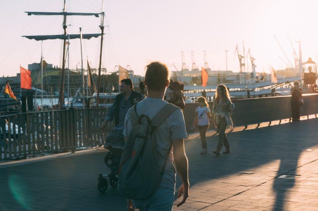 Rückansicht eines jungen Mannes  mit Rucksack, der eine städtische Flusspromenade entlang läuft. Im Hintergrund sind Boote sichtbar.