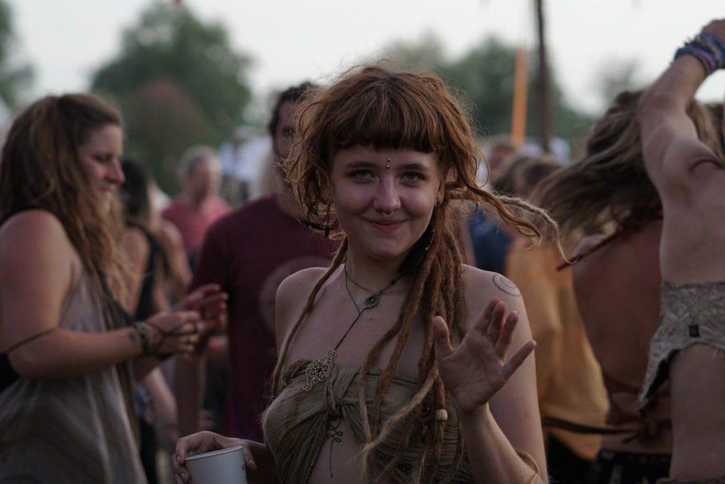 Ein Hippie-Mädchen steht in einer Menschenmenge auf einem Festival in Berlin und winkt lächelnd in die Kamera.