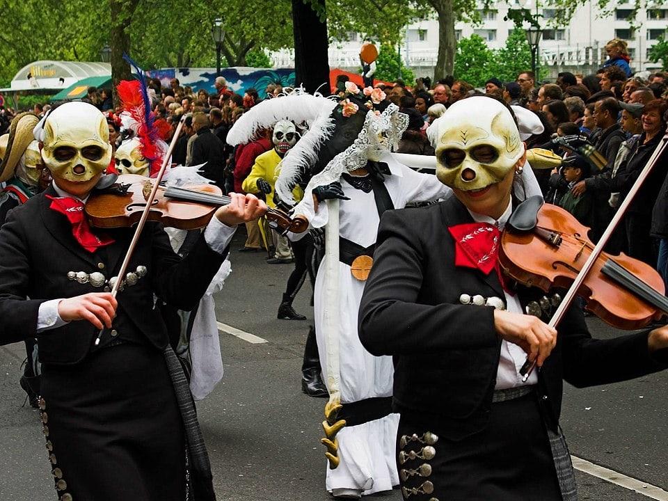 """Die Umzugsgruppe """"Calaca e. V."""" auf dem Karneval der Kulturen im Stil des mexiakischen Día de los Muertos mit Violinen und Totenkopfmasken."""