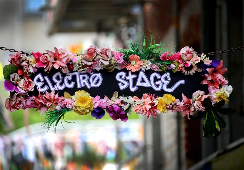 """Ein selbstgemachtes Schild mit der Aufschrift """"Elektro Stage"""" hängt an einer Kette über einer STraße. Das Schild ist mit Blumen verziert."""