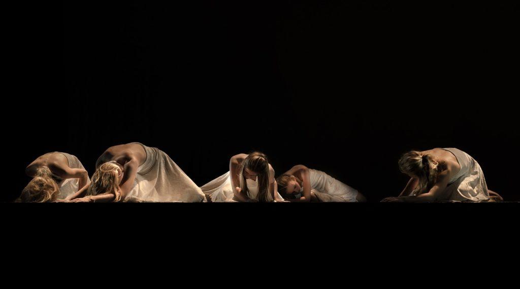 Moderne Tanz Performance auf einer Theatherbühne. Fünf junge Frauen in weißen Kleidern kauern auf dem Boden.